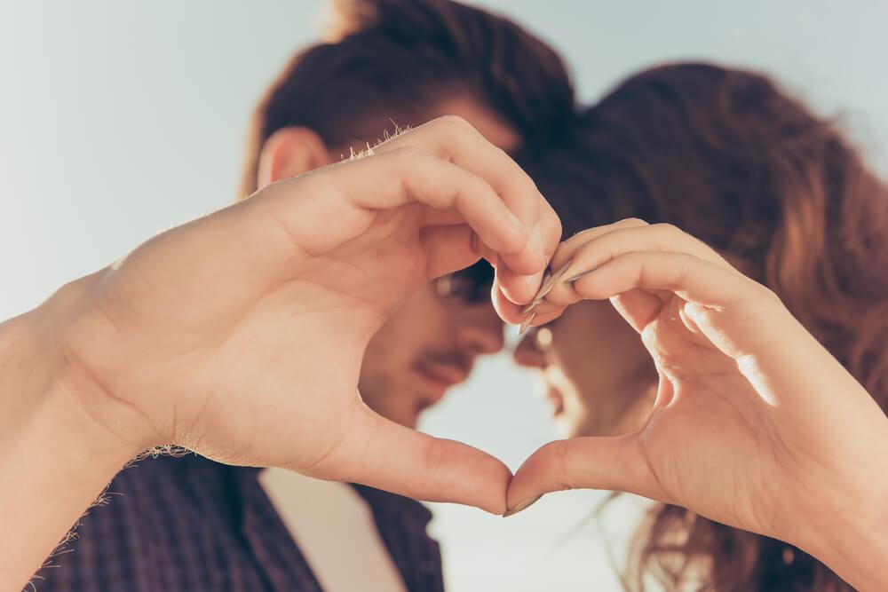 Pareja haciendo un corazón tras sentir amor a primera vista