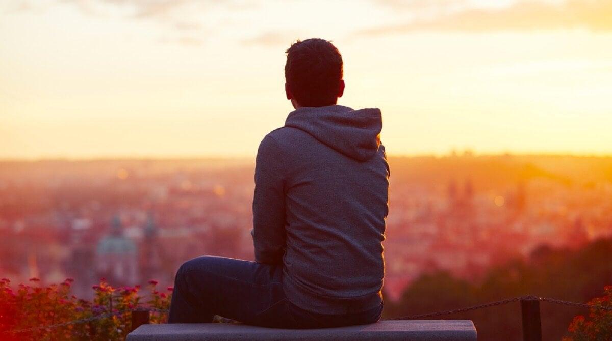 Joven mirando al horizonte pensando en sus problemas