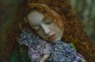 Mujer con los ojos cerrados con la cabeza apoyada en flores