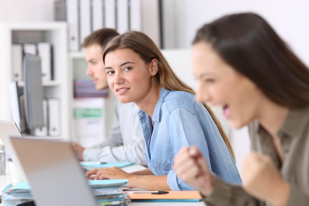 Mujer envidiando a una compañera de trabajo
