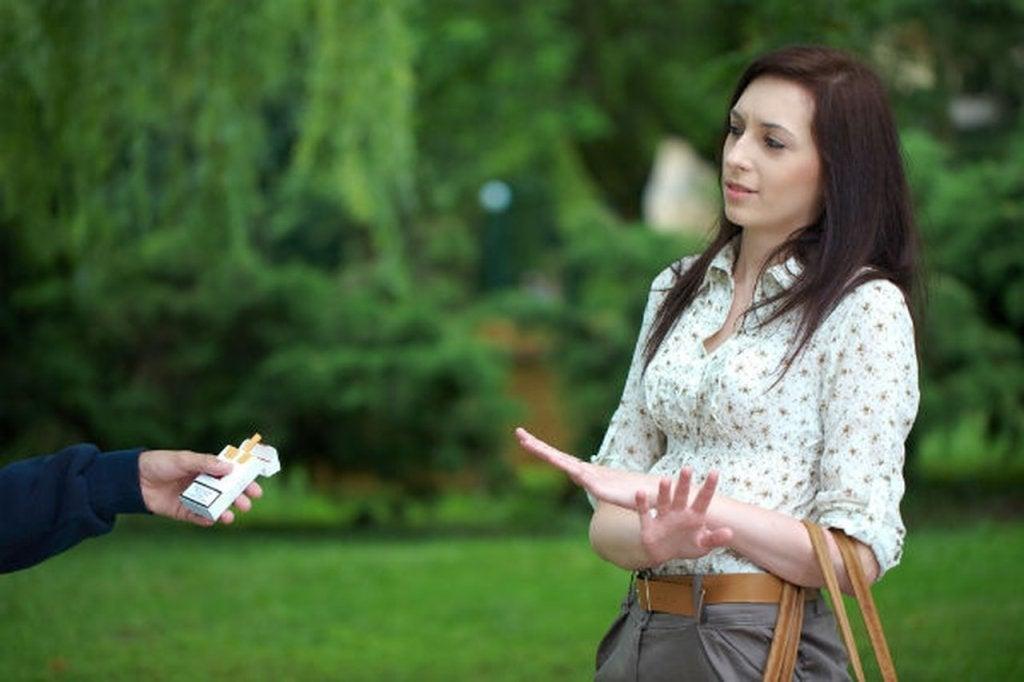 Mujer negándose a coger un cigarro
