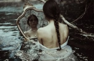 Mujer triste mirándose en un espejo