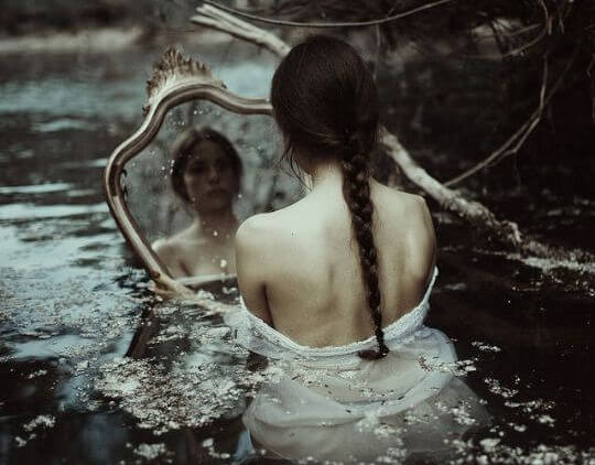 sad woman looking in the mirror in cold water.