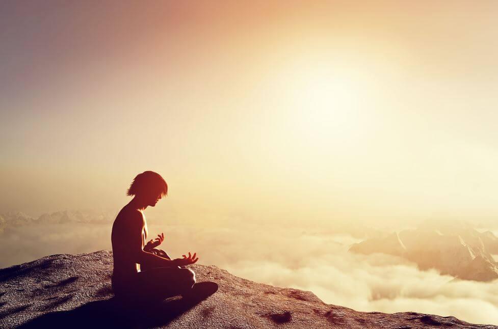 Hombre meditando en la cima de una montaña