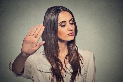 Mujer con la mano levantada en actitud de rechazo
