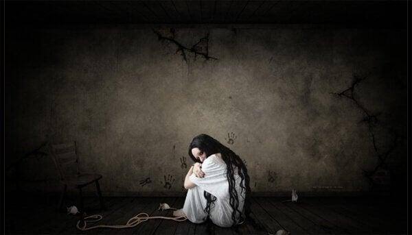 Mujer triste sentada en el suelo encogida