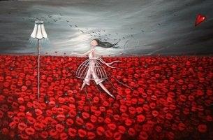 Niña andando por un campo de flores rojas