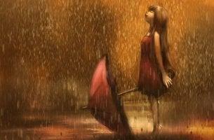 Chica sonriendo bajo la lluvia mostrando su desahogo emocional
