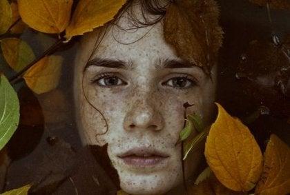 Chico entre hojas triste