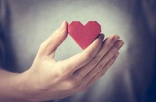 Corazón de papel en la mano representando el amor