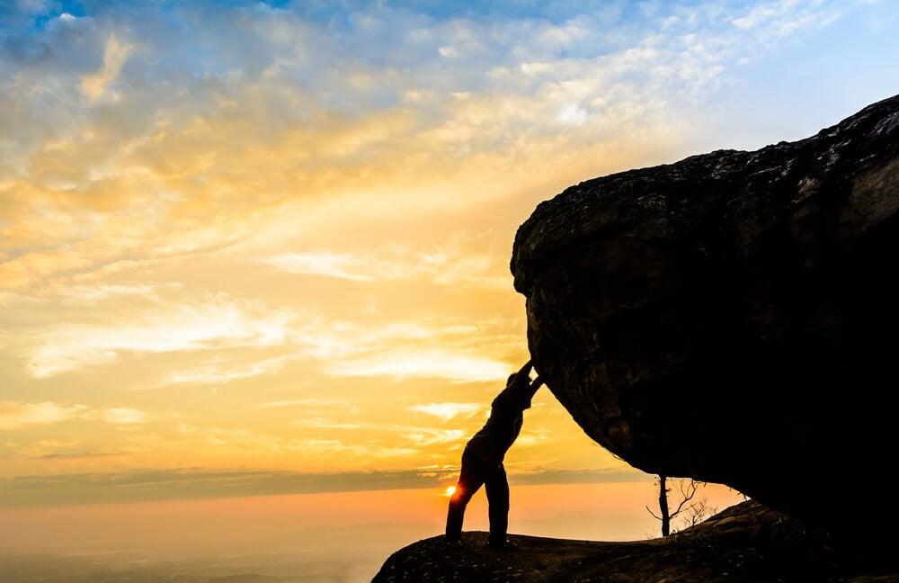 Hombre empujando una roca