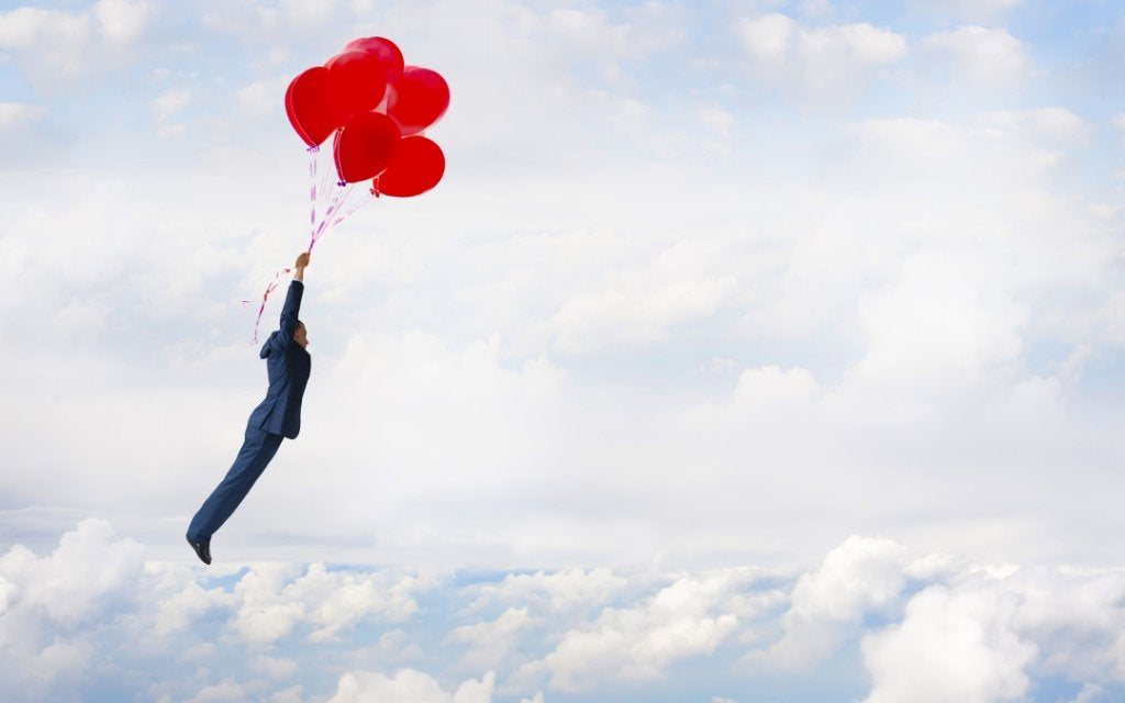 Hombre volando con globos