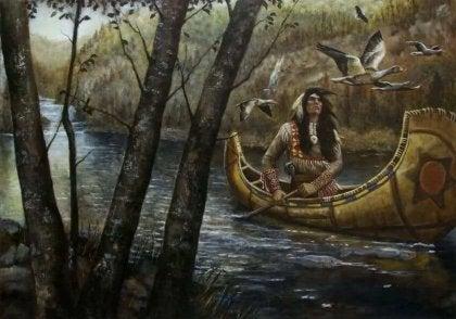 Indio navegando por el río con una canoa