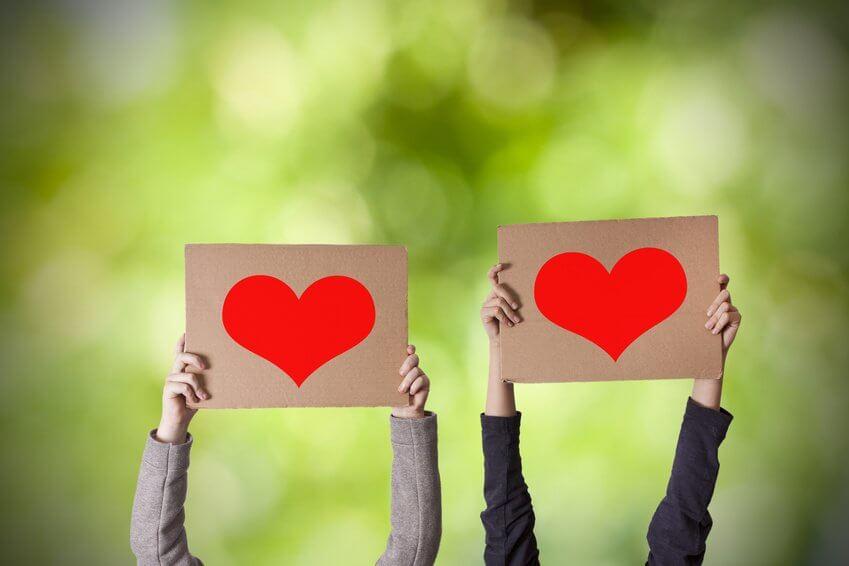 Manos sujetando carteles con corazones