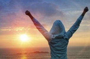 Mujer alzando los brazos tras leer frases de motivación