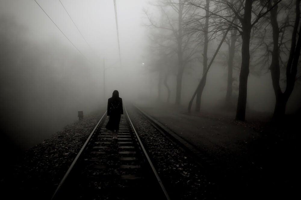 Mujer caminando por las vías del tren