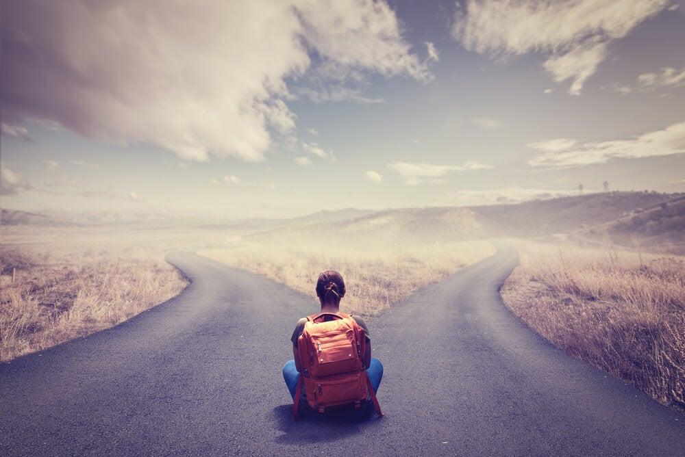 Mujer con mochila sentada frente a dos caminos que sufre aboulomanía