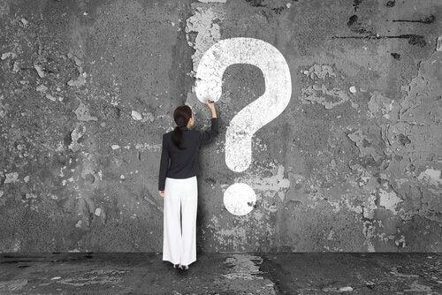 Mujer escribiendo una interrogación en la pared