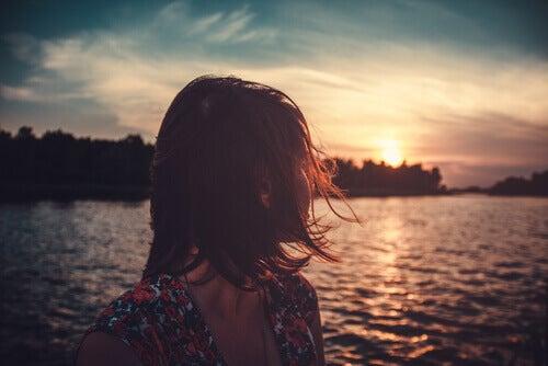 Mujer mirando hacia atrás para observar el atardecer