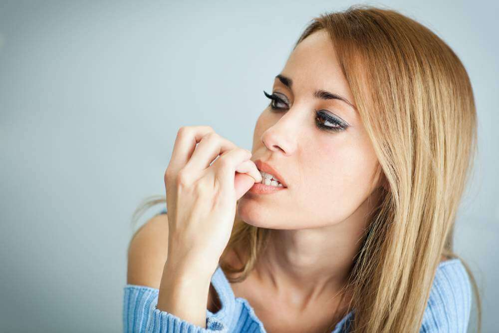 Mujer mordiéndose las uñas
