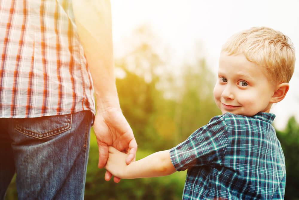 Niño cogiendo la mano de su padre y sonriendo