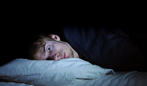 chico con insomnio intentando dormir