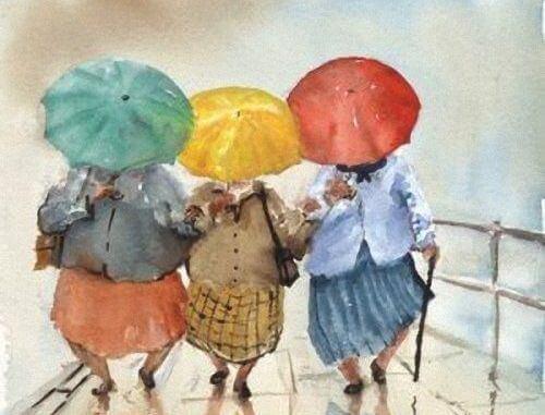 Tres mujeres con paraguas agarradas de las manos