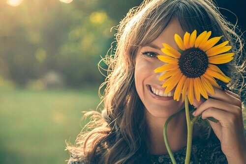 Mujer con un girasol sonriendo con felicidad