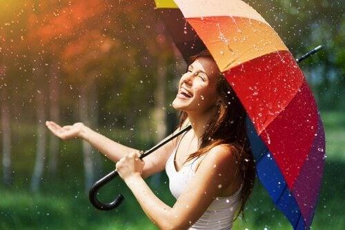 Mujer con paraguas de colores que conoce las enseñanzas de Albert ellis