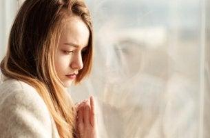 Mujer triste pensando en valorar la vida mientras mira por la ventana