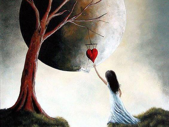 Niña cogiendo un corazón colgado de un árbol