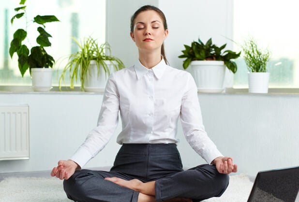 mujer en posición de loto practicando técnicas de respiración