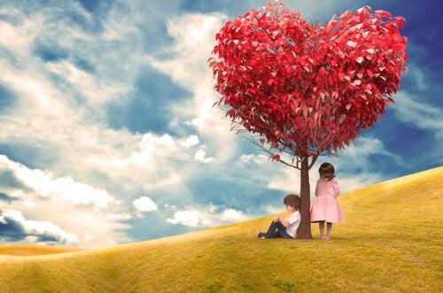 Chico sentado debajo del árbol del amor y chica de pie esperando