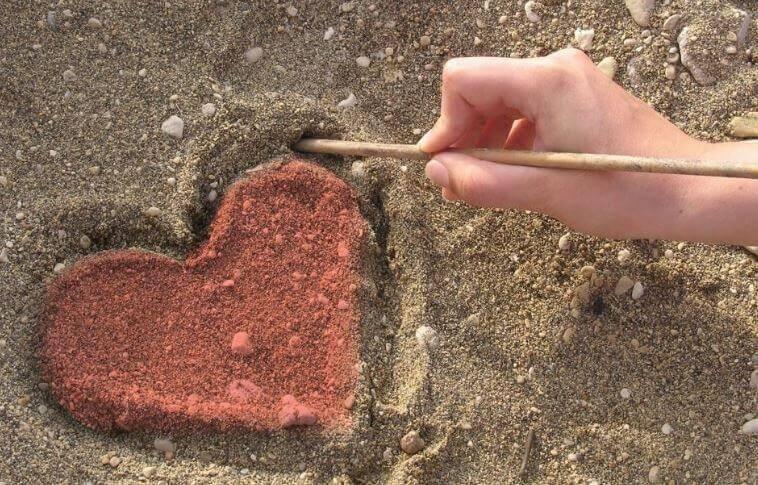 Mano dibujando un corazón en la arena simbolizando el arte de hacer el bien