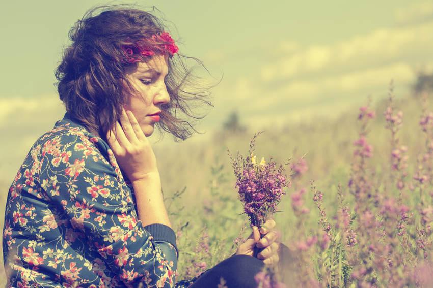 Mujer triste mirando un ramo flores