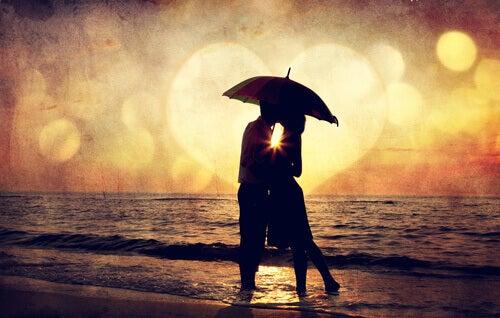 Pareja con un paraguas en la playa