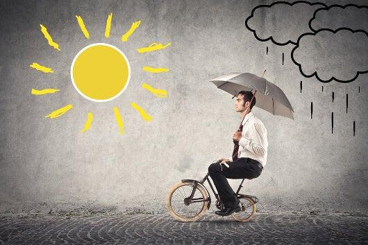 Hombre en bicicleta con paraguas bajo el sol