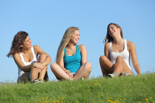 Amigas sentadas en el campo hablando
