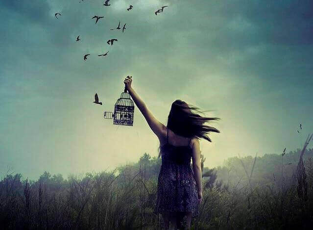 Mujer liberando pájaros y soltando la angustia