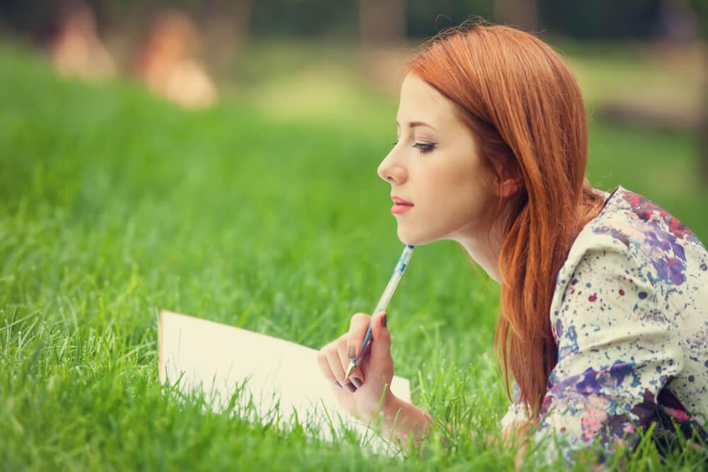 Mujer sobre el césped escribiendo
