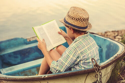 Niño leyendo en la playa