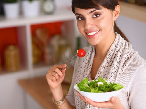 chica comiendo ensalada representando cómo la deficiencia de calcio y magnesio