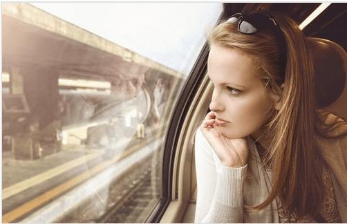 Chica joven mirando por la ventana del tren