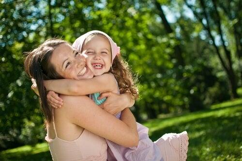 Madre enseñando a su hija a quererse más mientras la abraza