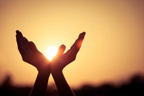Manos abiertas sosteniendo el sol al atardecer