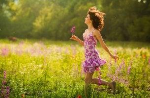 Mujer caminando entre flores sonriendo y feliz