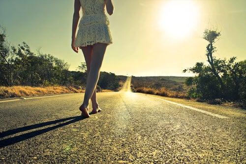 Mujer caminando sola en la carretera