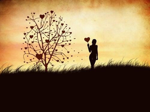 Mujer con globo de corazón en la mano junto al árbol de los sentimientos
