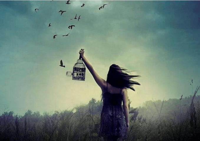 Mujer con jaula liberando pájaros