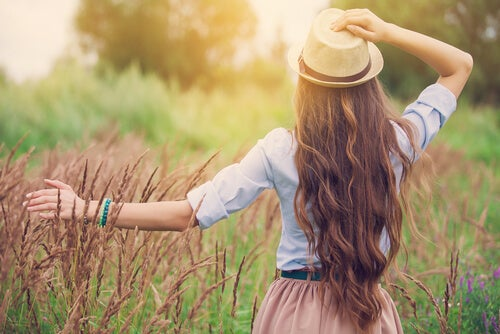 Mujer con sombrero caminando por sendero